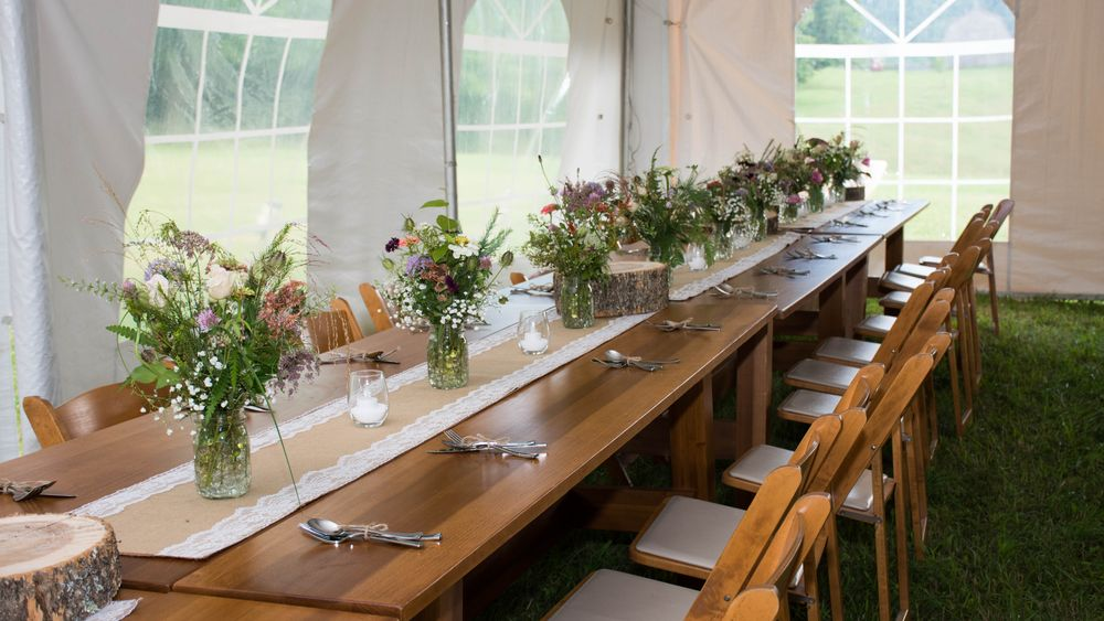 Farm tables bring together a custom outdoor reception set up.