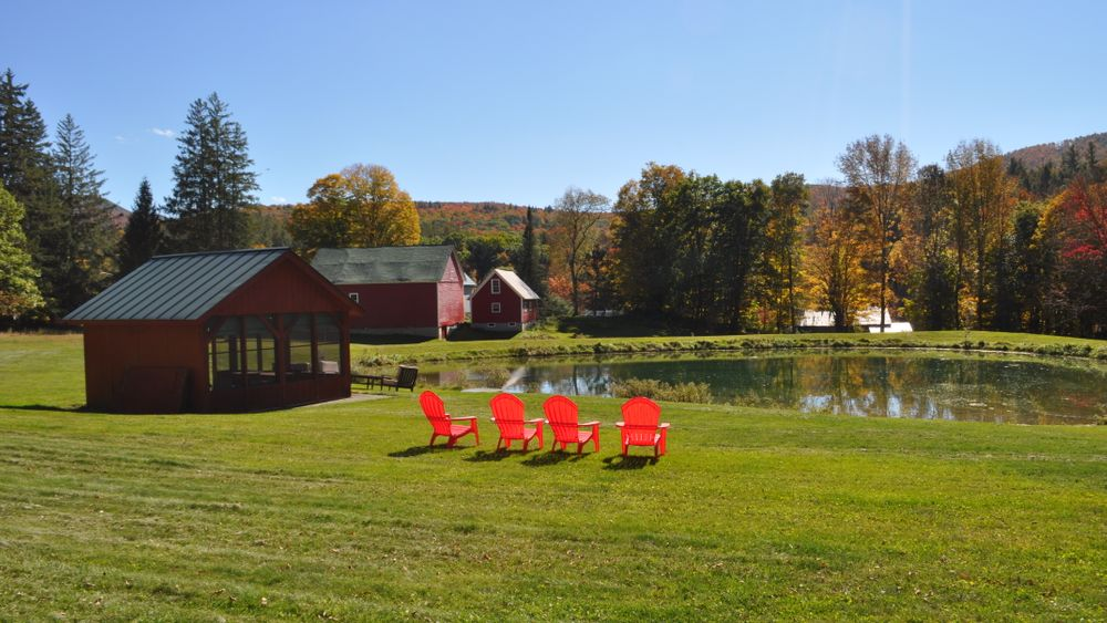 Enjoy the water view while relaxing in colorful adirondack chairs with a pond house and iconic red barn in the distance