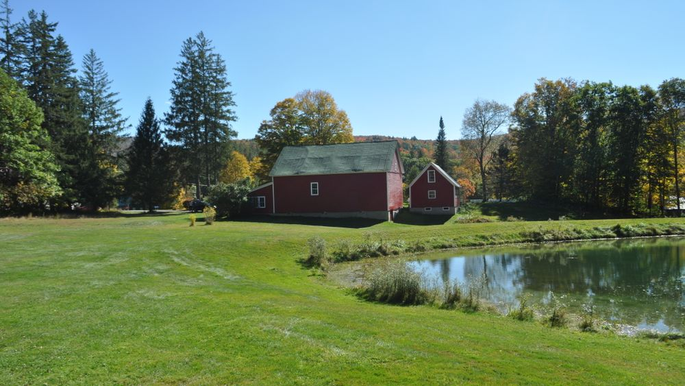 Small pond with iconic red barn in the distance