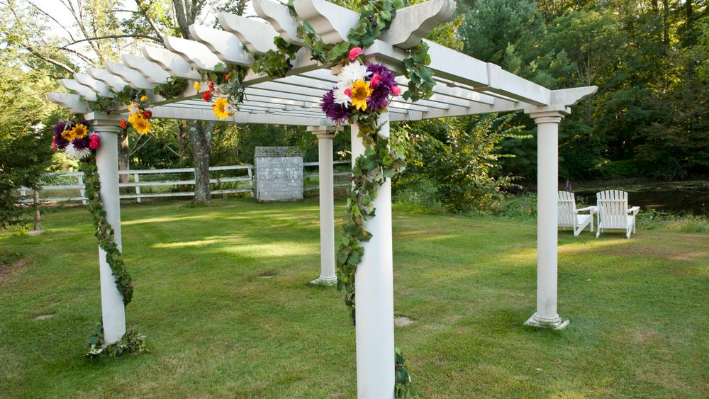 Fresh florals decorate the venue's pergola set in front of a small pond for a perfect ceremony backdrop. (Simi Rabinowitz Photography)