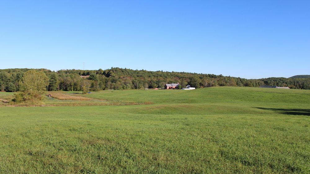 View from hilltop event area to historic barn, mountains.