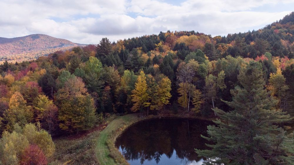Aerial view of surrounding mountains and fall foliage.