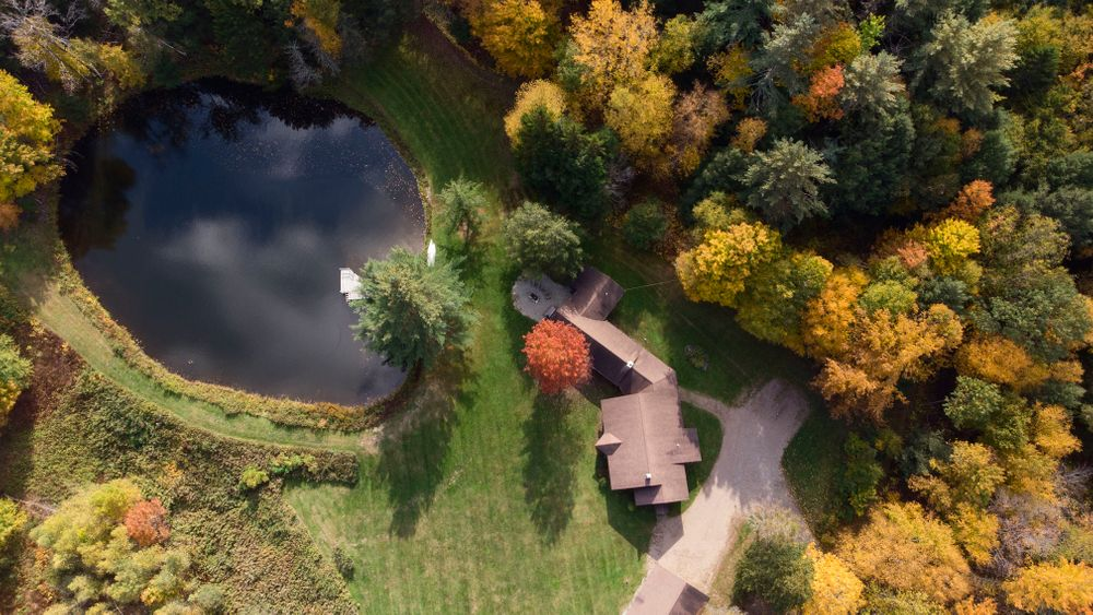 Aerial view of Main home, rustic cabin, pond and grounds.