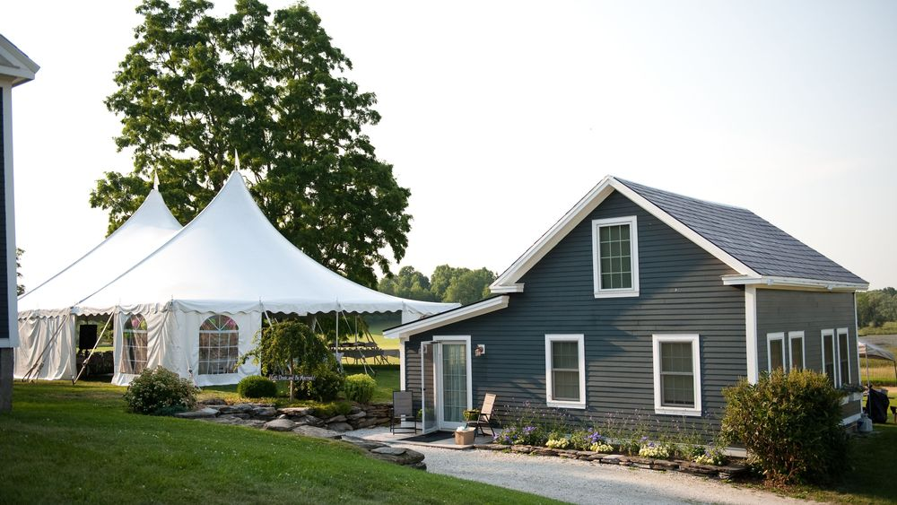 Side view of the tented wedding reception. The house to the left is the main house and the one to the right is the cottage available to rent. Photo Credit: Kat Mooney Photography