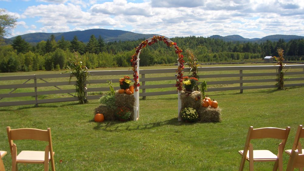 Ceremonial arch over iconic mountain view in front of split rail fencing.